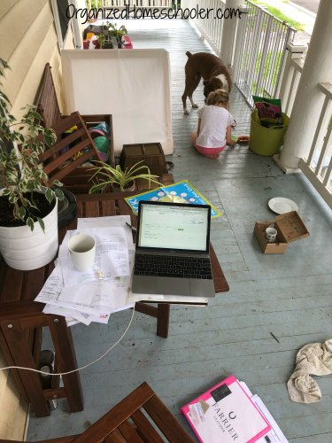 Working homeschool mom, daughter, and dog all working and learning together on the front porch.