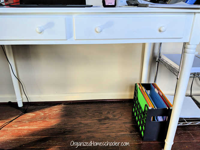 Organizing homeschool paperwork under a desk in a home office